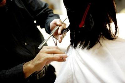 Мастер состригает кончики волос